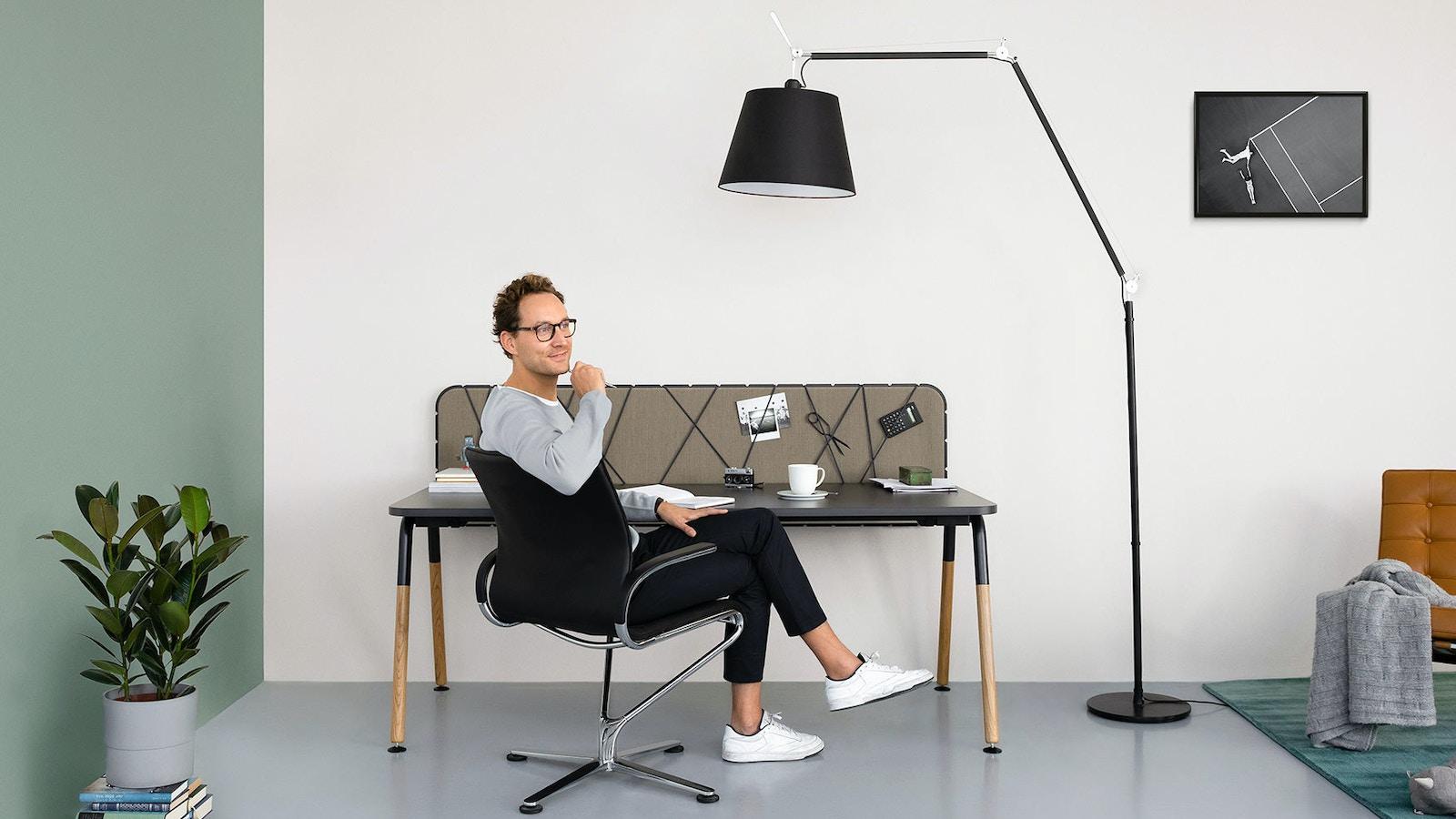 Ein junger Mann mit braunen Locken und Brille sitzt an einem Arbeitstisch. Er trägt einen grauen Pullover und eine schwarze Hose. Er lehnt sich mit dem rechten Ellbogen seitlich an die Rückenlehne seines schwarzen Drehstuhls, die Beine hat er überschlagen und sieht nachdenklich in die Ferne. Der Arbeitstisch hat eine schwarze Tischplatte, Beine aus hellem Holz und eine braune Pinnwand. Links neben dem Tisch gibt es eine grüne Wand, vor der auf einem Stapel Bücher eine Topfpflanze steht. Rechts neben dem Tisch steht eine große schwarze Stehlampe. Daneben liegt ein grüner Teppich, auf dem ein brauner Loungestuhl zu sehen ist.